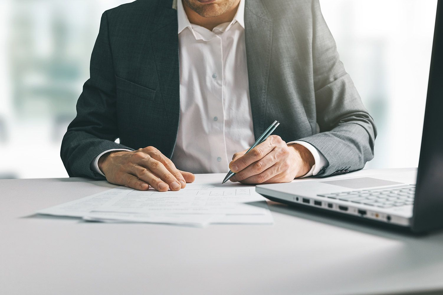Man in suit writing business papers at desk in office