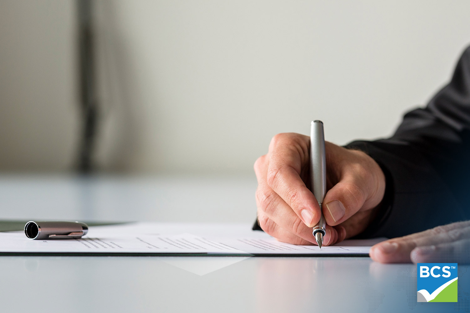 Wide panorama view of businessman hand signing insurance document