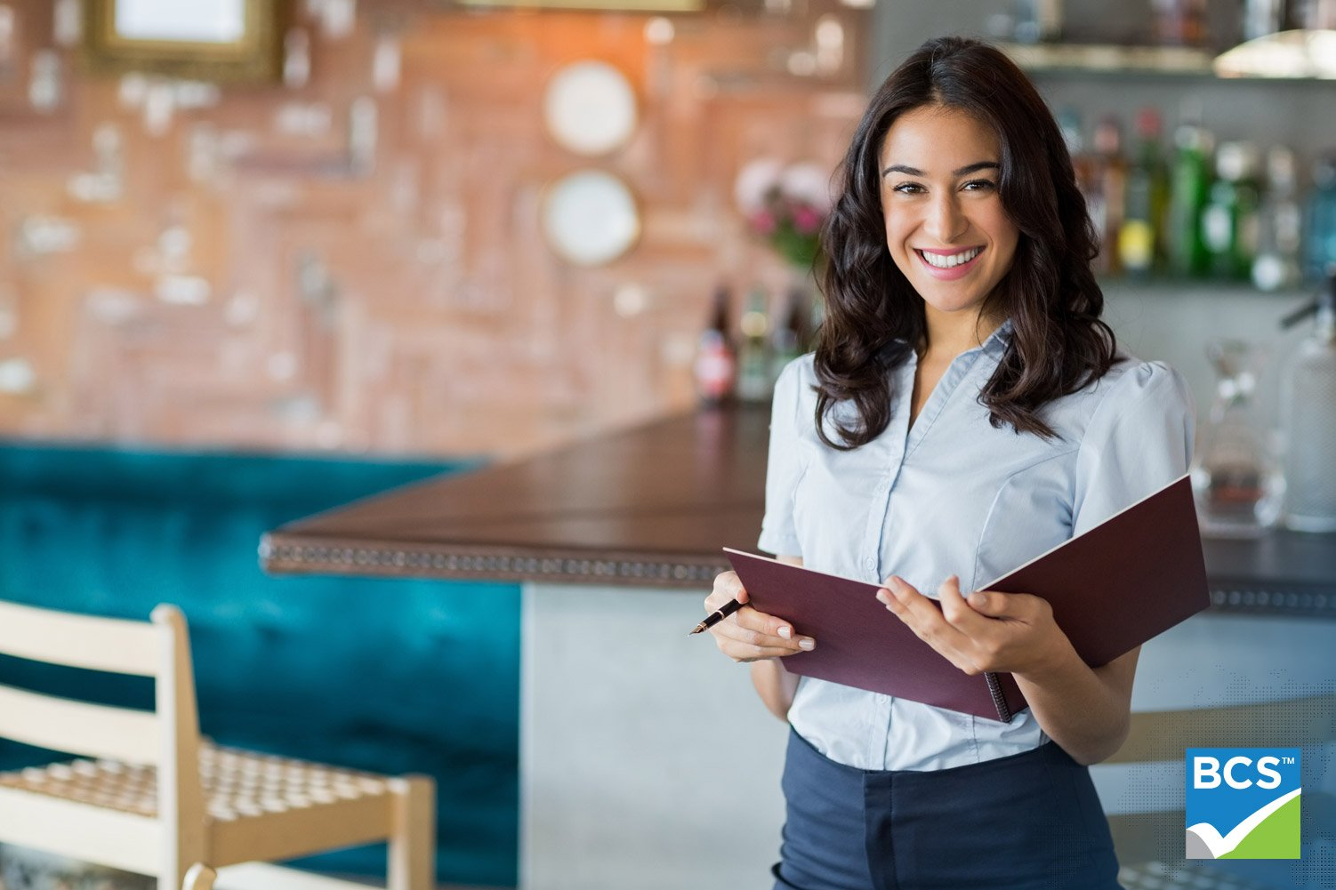 Smiling mixed race waitress holding a file