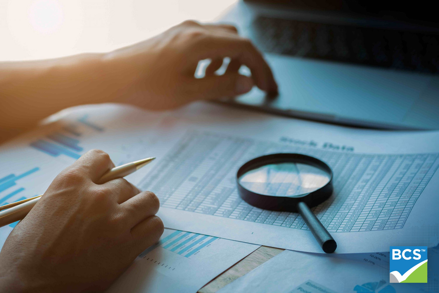 man looking at documents with magnifying glass sitting on top of financial documents