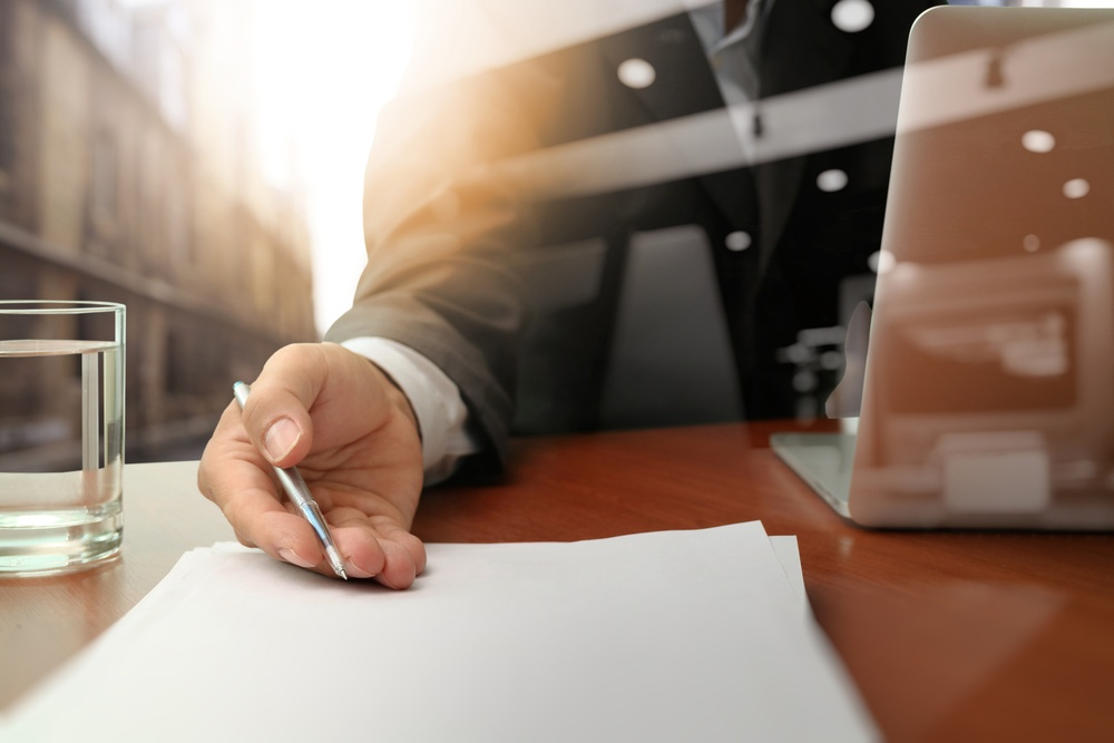 double exposure of businessman handing over a contract on wooden desk
