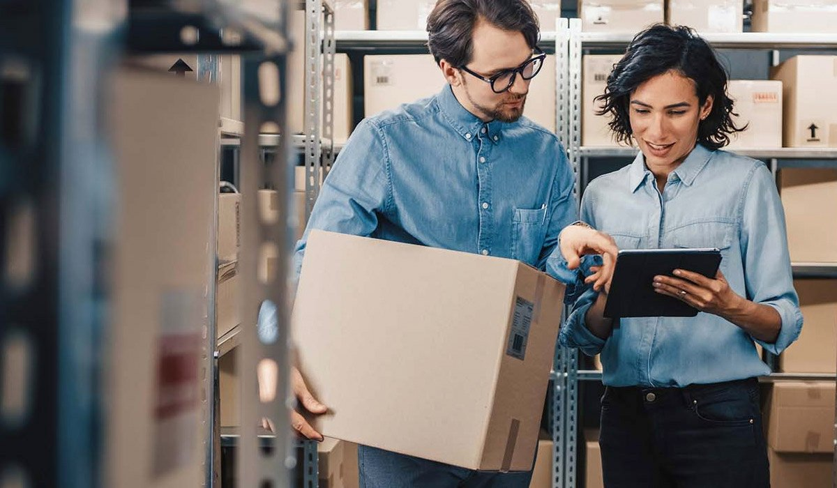 man-and-woman-looking-at-tablet-in-warehouse-setting